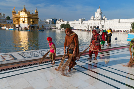 AMRITSAR, INDIA, DEC - 7, 2014: Unidentified Indian women and children clean floor near Golden Temple before the evening prayer. Harmandir Sahib also Darbar Sahib is the holiest Sikh gurdwara located in the city of Amritsar, Punjab, India.