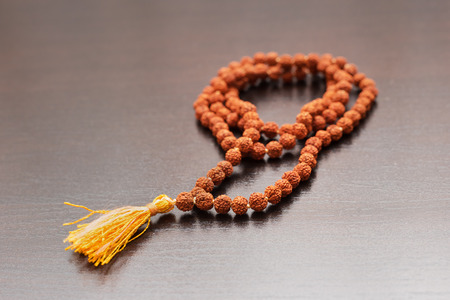 seed beads: Japa mala on the table. Prayer beads made from the seeds of the rudraksha tree Stock Photo