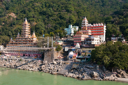 tera: RISHIKESH, INDIA - DEC 8, 2014: Tera Manzil Temple and Laxman Jhula bridge over Ganges river.  Rishikesh is  World Capital of Yoga,  has numerous yoga centres that also attract tourists