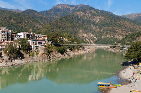 tera: RISHIKESH, INDIA - DEC 11, 2014: Laxman Jhula bridge over Ganges river.  Rishikesh is  World Capital of Yoga,  has numerous yoga centres that also attract tourists
