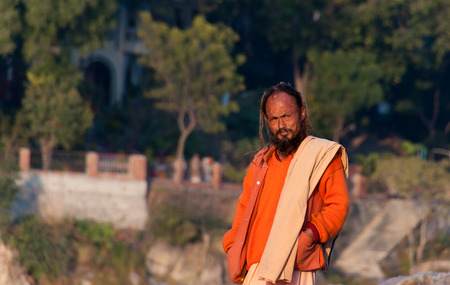 sadhu: RISHIKESH, INDIA - DEC 11, 2014: Unidentified Indian sadhu on the beach near River Ganga. Rishikesh is  World Capital of Yoga,  has numerous yoga centres that also attract tourists