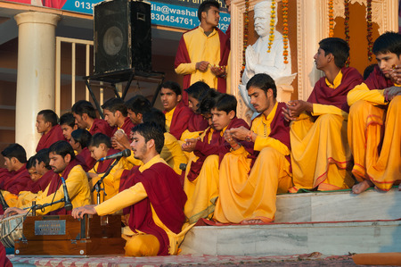 ashram: RISHIKESH, INDIA - DEC 12, 2014: Unidentified young novices on Ganga Aarti ceremony in Parmarth Niketan ashram at sunset. Rishikesh is World Capital of Yoga,  has numerous yoga centres that also attract tourists