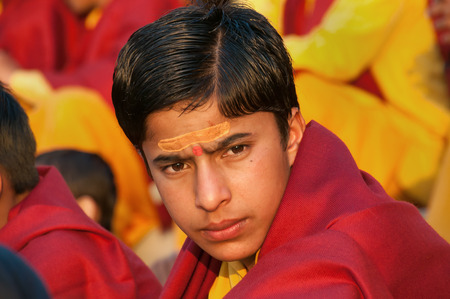 RISHIKESH, INDIA - DEC 12, 2014: Unidentified young novice on Ganga Aarti ceremony in Parmarth Niketan ashram at sunset. Rishikesh is World Capital of Yoga,  has numerous yoga centres that also attract tourists