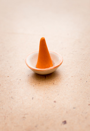 small plate: Small orange incense cone in small plate Stock Photo
