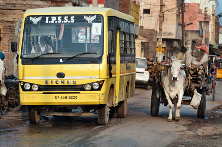 bullock: VRINDAVAN, INDIA - DEC 15, 2014:  Bullock cart and bus on the road. Vrindavan is considered to be a holy place. The major tradition followed in the area is Vaisnavism. It is the place where Krishna spent his childhood days.