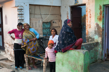 indian village: VRINDAVAN, INDIA - DEC 15, 2014: Unidentified Indian women and boy are near the house. Vrindavan is considered to be a holy place. The major tradition followed in the area is Vaisnavism. It is the place where Krishna spent his childhood days.
