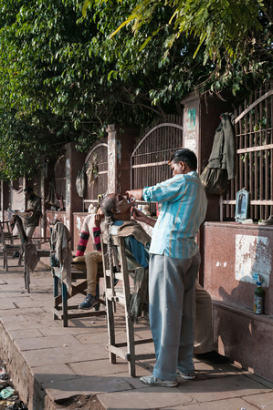 AGRA, INDIA - DEC 16, 2014: An unidentified street barbers shaving men on the street in market.  A lot of Indian poor people shave with a straight razor on the streets in India