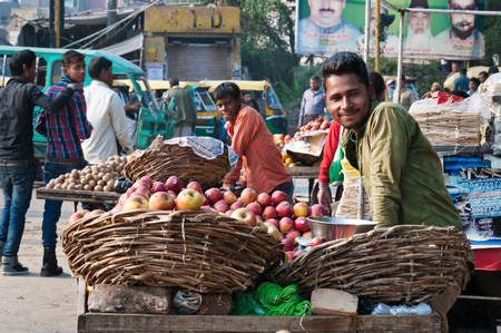AGRA, INDIA - DEC 16, 2014: An unidentified Indian vendor with fruit in market. Agra is major tourist destination because of its many splendid Mughal-era buildings, most notably the Taj Mahal, Agra Fort and Fatehpur Sikri Редакционное