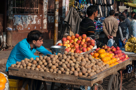 fatehpur sikri: AGRA, INDIA - DEC 16, 2014: An unidentified Indian vendor with fruit in market. Agra is major tourist destination because of its many splendid Mughal-era buildings, most notably the Taj Mahal, Agra Fort and Fatehpur Sikri Editorial