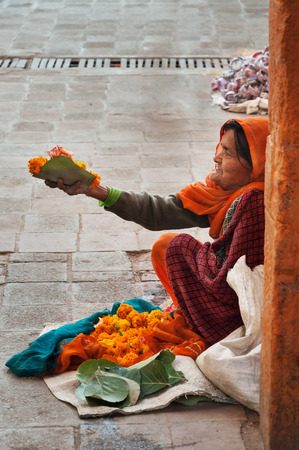 maharaja: ORCHHA, INDIA - DEC 19, 2015: Unidentified old poor woman sells garlands of flowers at the temple.Orchha is a town in Madhya Pradesh state? The town was established by Maharaja Rudra Pratap Singh in 1501
