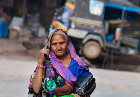 ORCHHA, INDIA - DEC 19, 2014: Unidentified Indian woman talking on mobile phone on the street