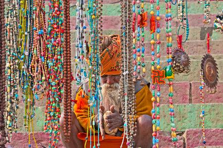 varanasi: VARANASI, INDIA - DEC 23, 2014: Indian Sadhu prepares dough for chapati on a ghat on the banks of the holy river Ganges in Varanasi