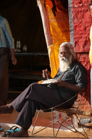 khajuraho: KHAJURAHO, INDIA - DEC 21, 2014: Old man eating a meal in street market. Khajuraho is small town with  Khajuraho Group of Monuments located in the Indian state of Madhya Pradesh Editorial
