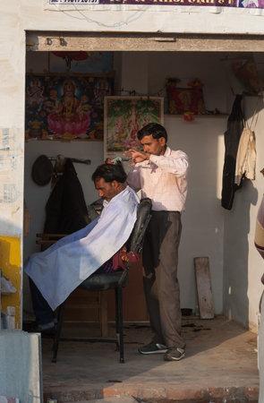 khajuraho: Khajuraho, India - 21 de diciembre 2014: El peluquero profesional UnidentifiedIndian en el sal�n de la calle. Khajuraho es peque�a ciudad con Khajuraho ubicadas en el estado indio de Madhya Pradesh Editorial