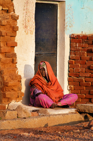 khajuraho: KHAJURAHO, INDIA - DEC 21, 2014: Unidentified Indian woman in orange sari sits on a house porch. Khajuraho is small town with  Khajuraho Group of Monuments located in the Indian state of Madhya Pradesh