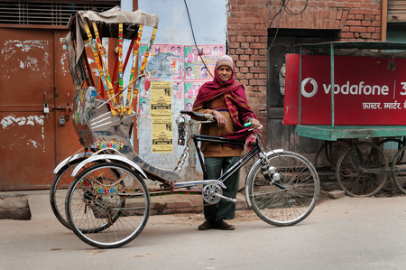 jainism: VARANASI, INDIA - DEC 23, 2014: Trishaw driver on the street cold foggy morning in winter at Varanasi, Uttar Pradesh. Varanasi  is the holiest of the seven sacred cities in Hinduism and Jainism. Hindus believe that death at Varanasi brings salvation.