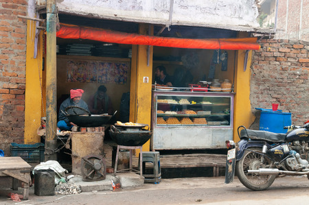 culinary tourism: VARANASI, INDIA - DEC 23, 2014: Local sweet and snack shop in Varanasi. Uttar Pradesh. Varanasi  is the holiest of the seven sacred cities in Hinduism and Jainism.