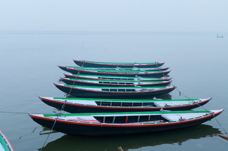 uttar: Boats in a row on sacred river Ganges foggy morning. Varanasi. Uttar Pradesh, India