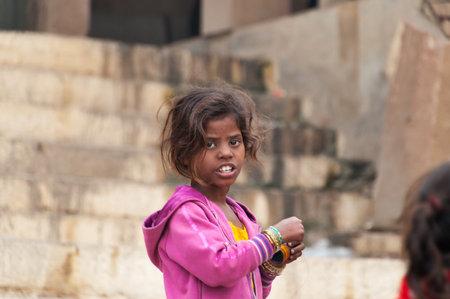 varanasi: VARANASI, INDIA - DEC 23, 2014: Unidentified Indian young girl on the Ghat in Varanasi. Uttar Pradesh, India