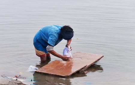 varanasi: VARANASI, INDIA - DEC 23, 2014: Unidentified Indian man washes clothes in the holy water of the river Ganges in Varanasi. Uttar Pradesh, India Editorial