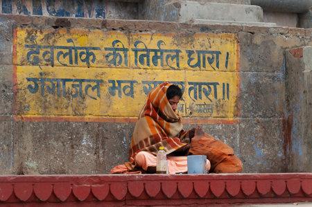 uttar: VARANASI, INDIA - DEC 23, 2014: Unidentified Indian man sits on the steps of ghat near sacred river Ganges in Varanasi. Uttar Pradesh, India