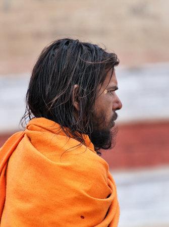 VARANASI, INDIA - DEC 23, 2014: Unidentified Indian young Sadhu on the street in Varanasi. Uttar Pradesh, India