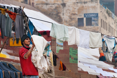 ghat: VARANASI, INDIA - DEC 23, 2014: Unidentified Indian man hang the wash on clothesline on ghat near sacred river Ganges in Varanasi. Uttar Pradesh, India Editorial