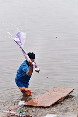benares: VARANASI, INDIA - DEC 23, 2014: Unidentified Indian man washes clothes in the holy water of the river Ganges in Varanasi. Uttar Pradesh, India Editorial