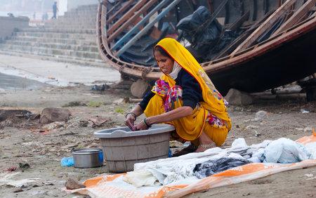uttar: VARANASI, INDIA - DEC 23, 2014: Unidentified Indian woman washes clothes on ghat near sacred river Ganges in Varanasi. Uttar Pradesh, India