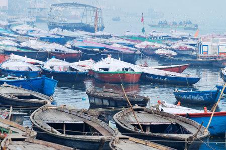 uttar: VARANASI, INDIA - DEC 23, 2014: Boats on sacred river Ganges foggy morning. Varanasi. Uttar Pradesh, India Editorial