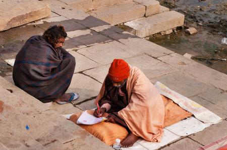uttar: VARANASI, INDIA - DEC 23, 2014: Unidentified Indian men sits on the ghat near sacred river Ganges in Varanasi. Uttar Pradesh, India