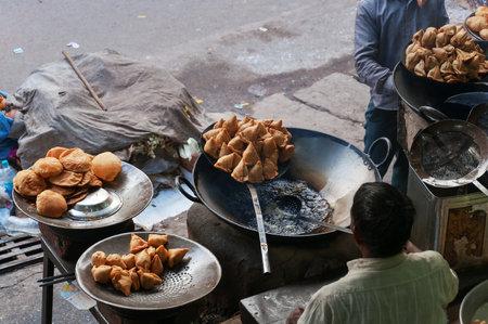 vendedor: VARANASI, INDIA - 23 de diciembre 2014: comida de la calle de la India en el mercado de la calle. Varanasi. Uttar Pradesh. India