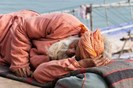 uttar: VARANASI, INDIA - DEC 23, 2014: Unidentified Indian man sleeps on the ghat near sacred river Ganges in Varanasi. Uttar Pradesh, India