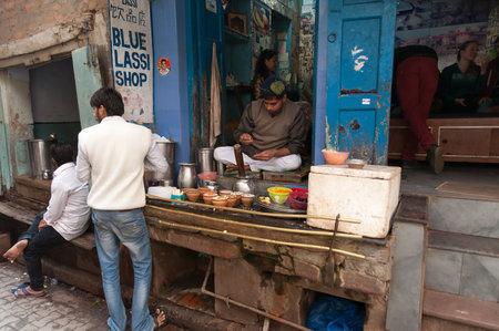 milkman: VARANASI, INDIA - DEC 23, 2014: Unidentified Indian milkman prepares the popular drink lassi in Blue lassi shop in the old city of Varanasi. Uttar Pradesh, India