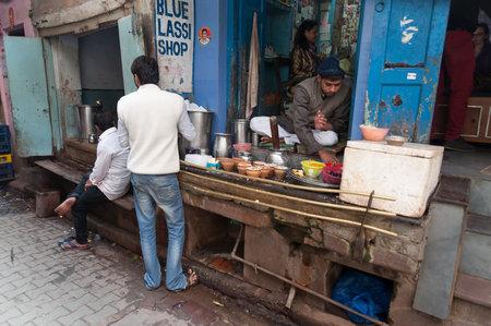 varanasi: VARANASI, INDIA - DEC 23, 2014: Unidentified Indian milkman prepares the popular drink lassi in Blue lassi shop in the old city of Varanasi. Uttar Pradesh, India