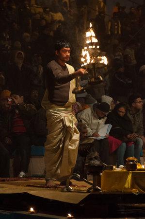 benares: VARANASI, INDIA - DEC 23, 2014: Unidentified Indian priest performs religious Ganga Aarti ceremony or fire puja at Dashashwamedh Ghat in Varanasi. Uttar Pradesh