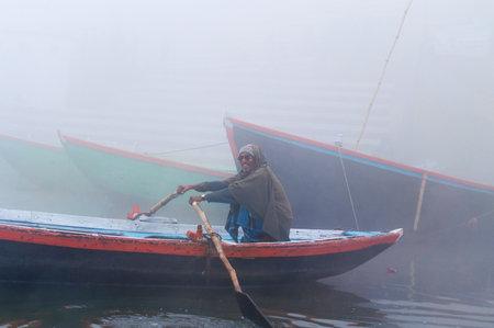 uttar: VARANASI, INDIA - DEC 24, 2014: Unidentified Indian man sailing on the boat on sacred river Ganges at cold foggy winter morning. Varanasi. Uttar Pradesh
