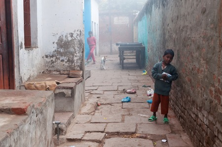 jainism: VARANASI, INDIA - DEC 24, 2014: Unidentified Indian boy on the street cold foggy winter morning in Varanasi. Uttar Pradesh. Varanasi  is the holiest of the seven sacred cities in Hinduism and Jainism.