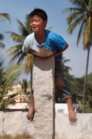 karnataka culture: BANGALORE, INDIA - DEC 26, 2014: Unidentified Indian boy on stone pillar on the street in Bangalore.  Karnataka. India