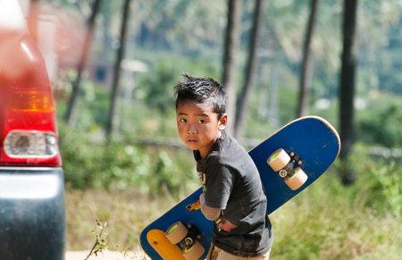 karnataka culture: BANGALORE, INDIA - DEC 26, 2014: Unidentified Indian boy with  skateboard on the street in Bangalore.  Karnataka. India Editorial