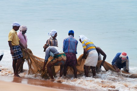 kovalam: KOVALAM, INDIA - DEC 28, 2014: Unidentified Fishermen pull their fishing net on Samudra beach in Kovalam. Kerala. India