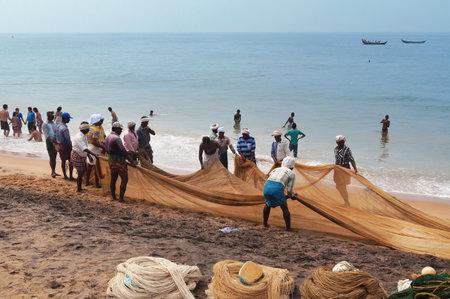 kovalam: KOVALAM, INDIA - DEC 28, 2014: Unidentified Fishermen pull their fishing net on Samudra beach in Kovalam. Kerala. India