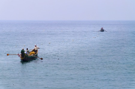 kovalam: KOVALAM, INDIA - DEC 28, 2014: Traditional wooden fishing boats in the ocean. Kovalam. Kerala. India