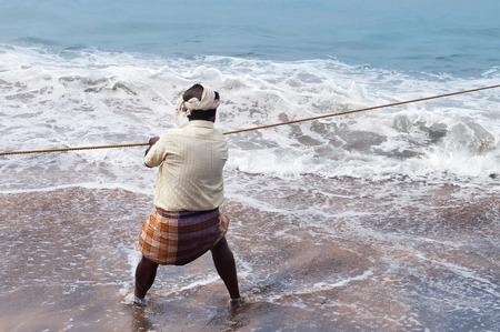 kovalam: KOVALAM, INDIA - DEC 28, 2014: Unidentified Fisherman pulls fishing net on Samudra beach in Kovalam. Kerala. India