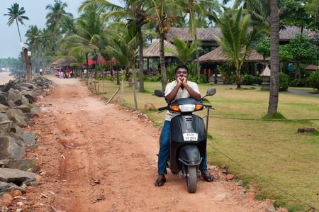 kovalam: KOVALAM, INDIA - DEC 28, 2014: Unidentified Indian man on motorbike on the road next to the Samudra beach. Kovalam. Kerala. India Editoriali