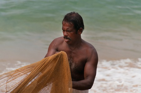 kovalam: KOVALAM, INDIA - DEC 28, 2014: Unidentified Indian Fisherman with fishing neton Samudra beach in Kovalam. Kerala. India