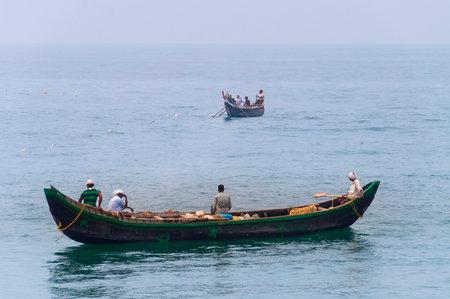 kovalam: KOVALAM, INDIA - DEC 28, 2014: Traditional wooden fishing boats in the ocean. Kovalam. Kerala. India