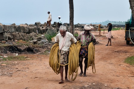kovalam: KOVALAM, INDIA - DEC 28, 2014: Unidentified Fishermen with a rope for fishing net  on Samudra beach in Kovalam. Kerala. India