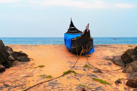 kovalam: Fishing  Boat on Tropical beach in Kovalam. Kerala. India Stock Photo