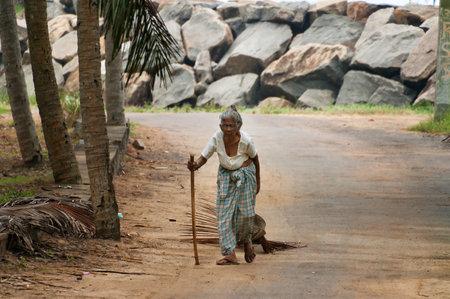 kovalam: KOVALAM, INDIA - DEC 28, 2014: Unidentified Indian elderly woman walking along the road in the fishing village. Kovalam. Kerala